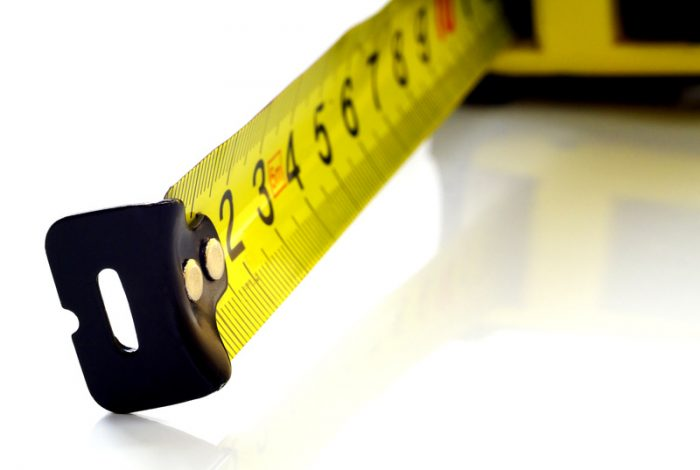 Self-retracting tape measure on white background, closeup, shallow depth of field